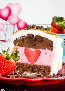 chocolate pound cake baked alaska with a heart shaped strawberry inside and a blue colander of berries