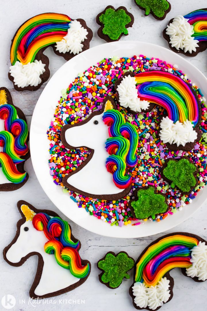 chocolate unicorn and rainbow cookies on a plate of sprinkles withminiature sparkly green clover cookies
