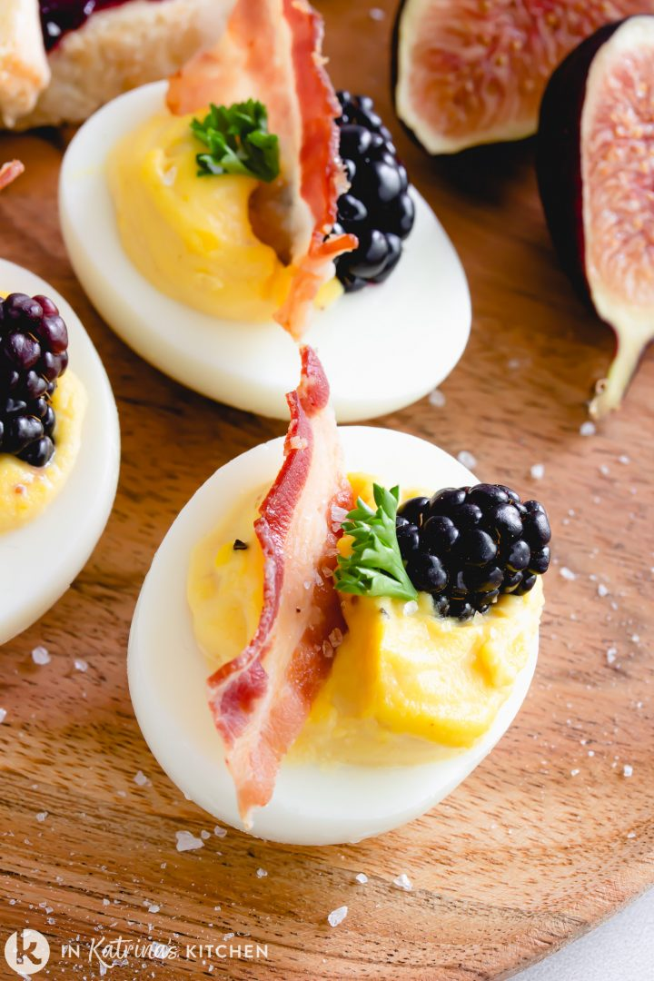 deviled eggs with bacon and berries shown on a wooden platter and sprinkled with sea salt