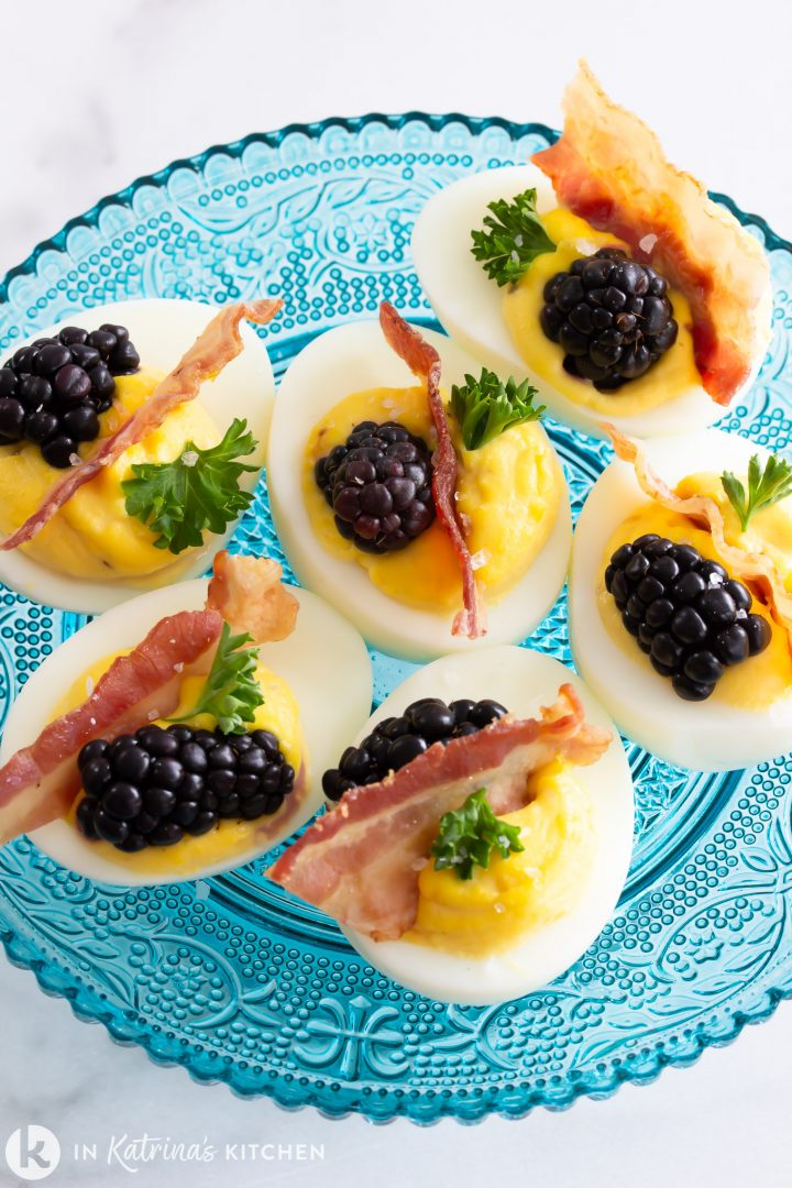 deviled eggs with blackberries and bacon on a blue plate