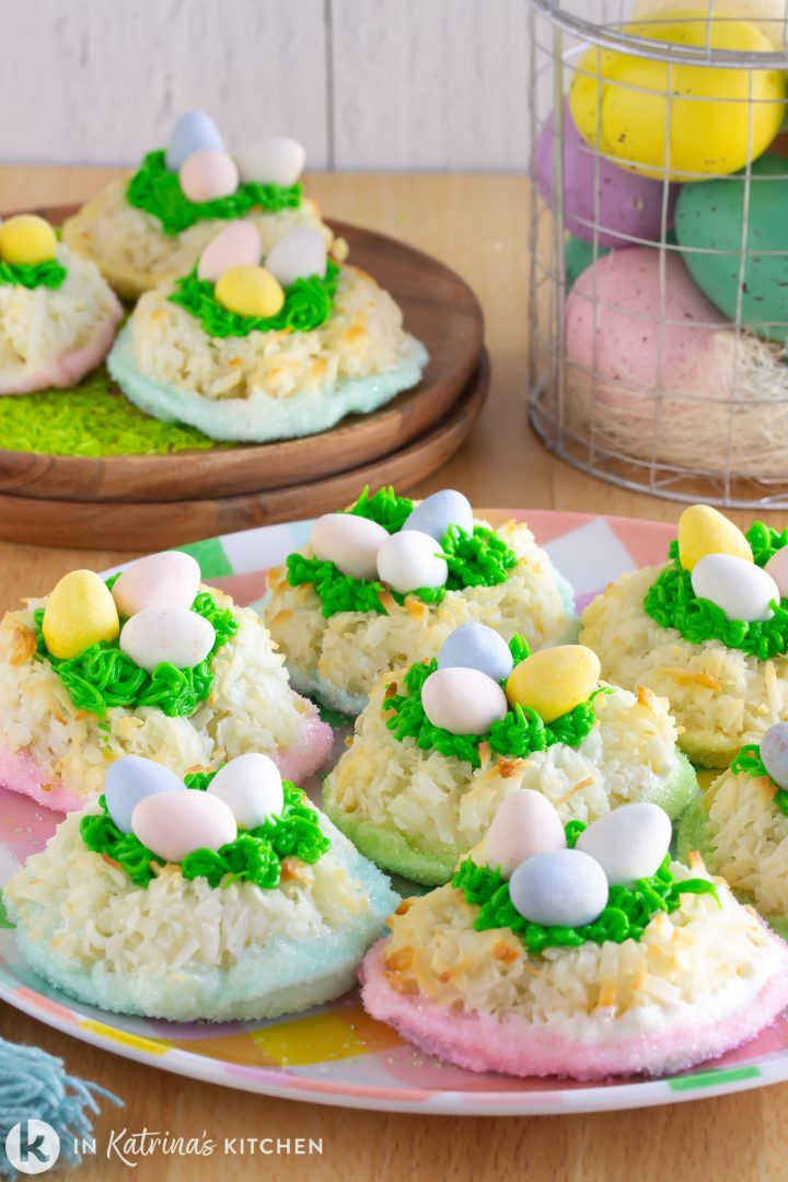 macaroon cookies dipped in white chocolate and pastel sprinkles made to look like nests with candy eggs on top