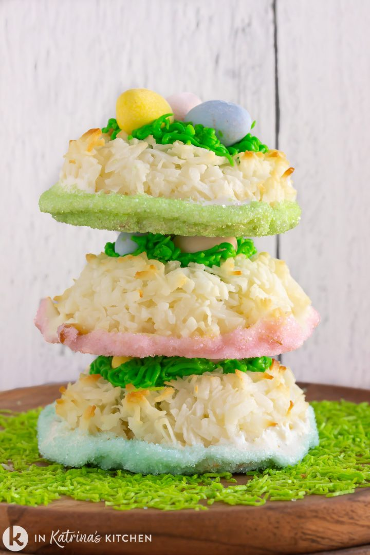 three white chocolate coconut macaroon cookies stacked on top of one another on a bed of green sprinkles