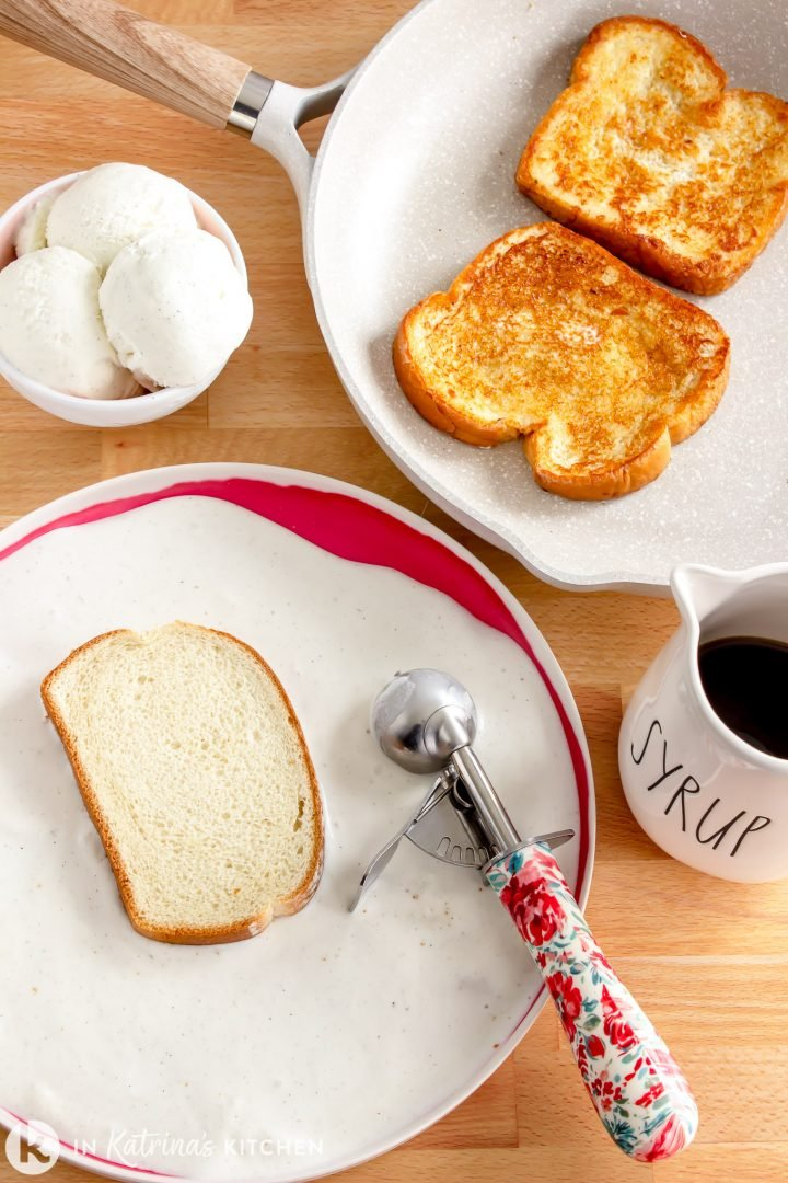 a slice of bread being dipped into melted ice cream near a pan with French Toast cooking