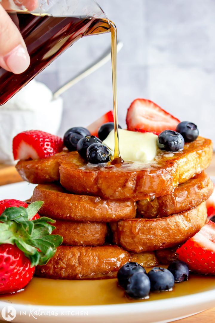 maple syrup being drizzled over pancakes with sliced strawberries and blueberries with vanilla ice cream in the background