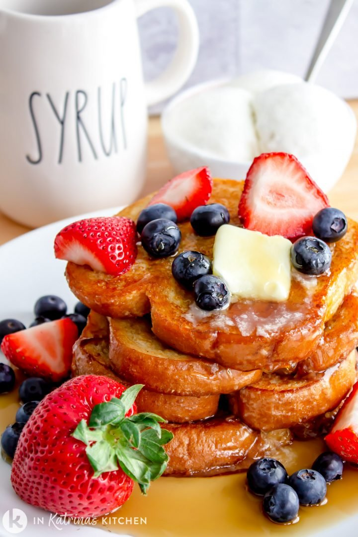 a stack of French toast with berries, butter, and syrup shown with a bowl of vanilla ice cream