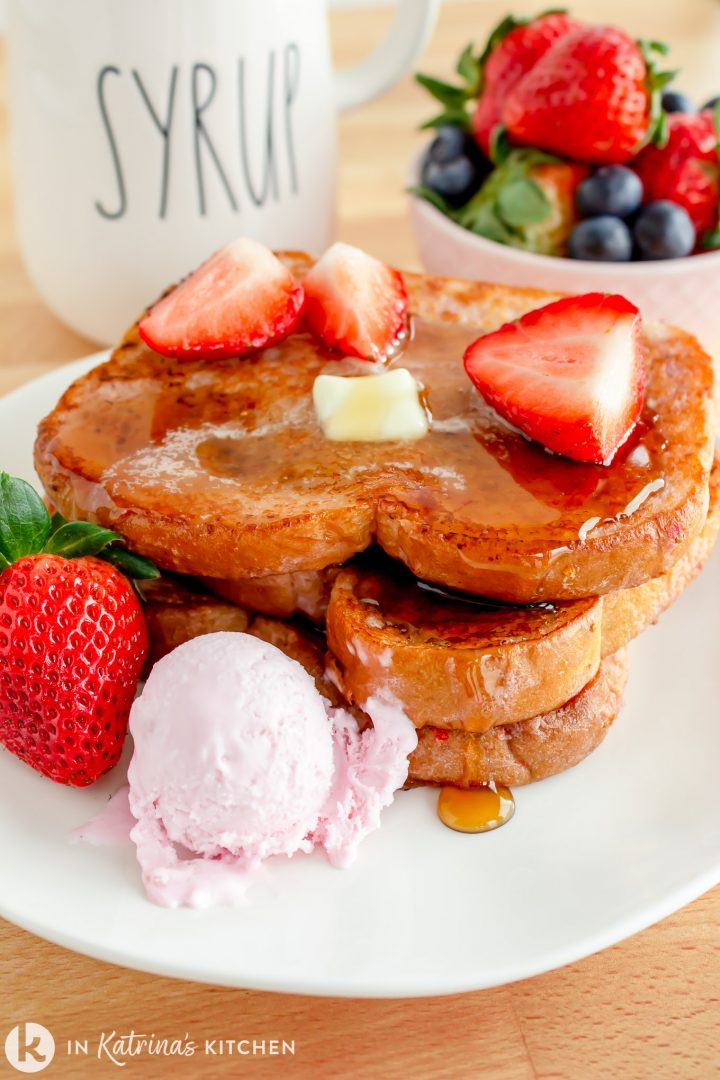 strawberry ice cream beside a stack of golden French Toast with melting butter and syrup