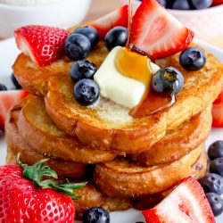 maple syrup poured on top of French toast with fresh berries and melting butter