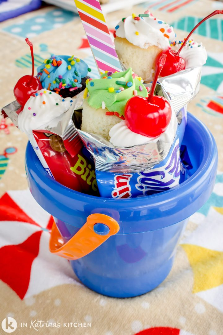 a blue beach pail with cookie bags full of ice cream sundae toppings